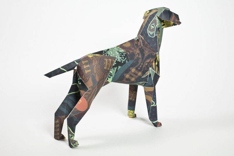 Back view of a paper dog sculpture in 3D form. A dark dog with colours such as dark brown, brown and green that has been inspired by sea foliage. The artist is Kristina Collantes who designed the pattern for an exhibition headed by design studio Lazerian