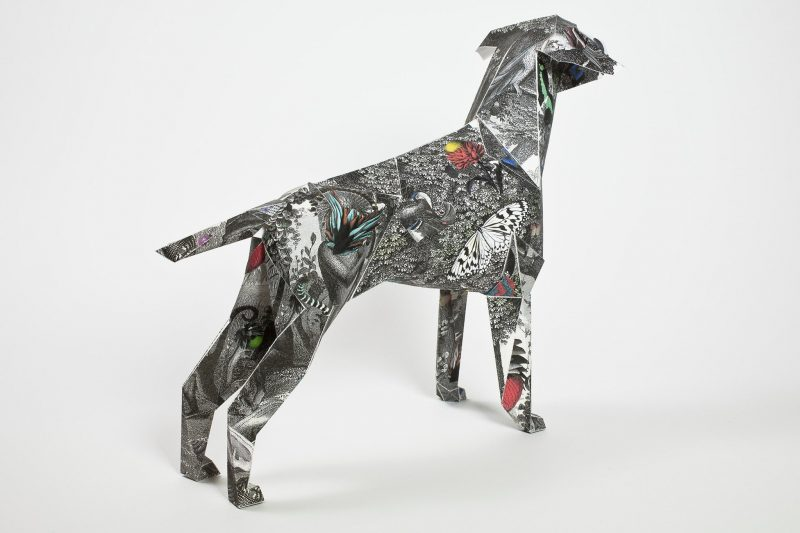 Back view of a black and white designed paper dog with a collection of animals all over it by artist Kristjana S Williams. Part of an international exhibition by design studio Lazerian. Artist and designers were all invited to customise the paper sculptures using their own signature styles.