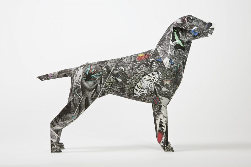 Side view of a black and white paper dog that is covered in animals and designed by international artist Kristjana S Williams. As part of an exhibition by design studio Lazerian where they asked artist and designers to contribute to the design exhibition by adding their signature styles to the paper dog.