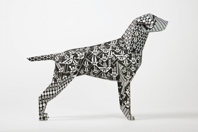 ISde view of a paper dog model from design studio Lazerian. The dog has a black and white designed pattern all over it.