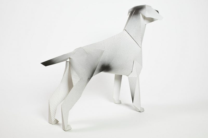 a backward view of a paper dog model sculpture n 3D form. the design on the cost is small lines that lead to bigger ones that look like ink sploshes from a distance