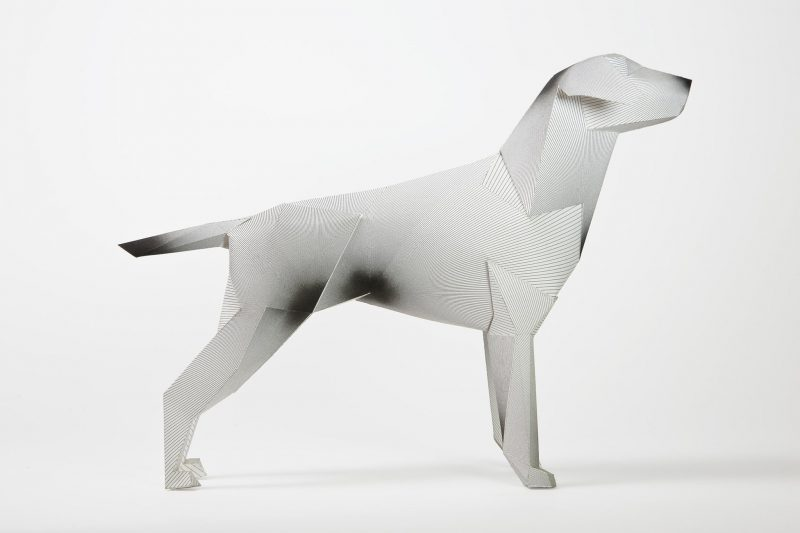 Side view of a white 3D paper dog sculpture with a design of lines on the bosy. some of the lines meet to create what appear like ink sploshes in several corner places.