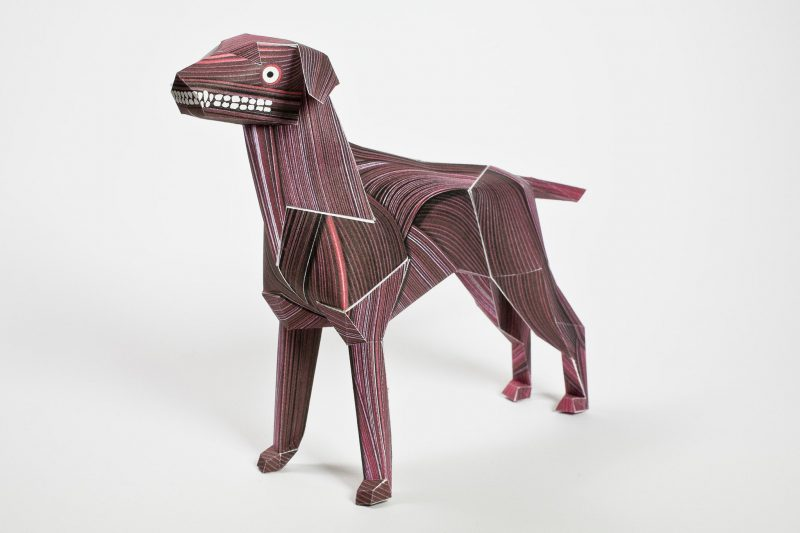 A red/burgundy wood venner type of look on this paper dog model who also has a round eye and a grimacing grin complete with teeth on offer!