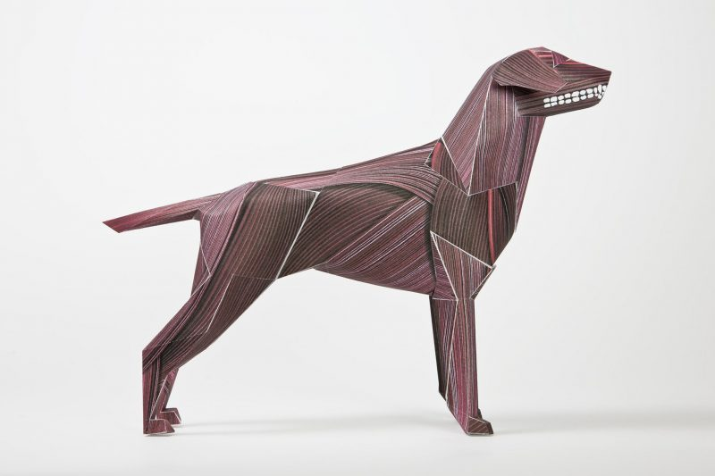 A side view of a paper dog model who is dark red in colour and has a line effect drawn on its paper to create a wood veneer look.