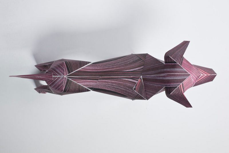 Over head view of a 3D paper dog model who is dark red in colour and has the effect of a wood veneer due to lines being drawn on its coat