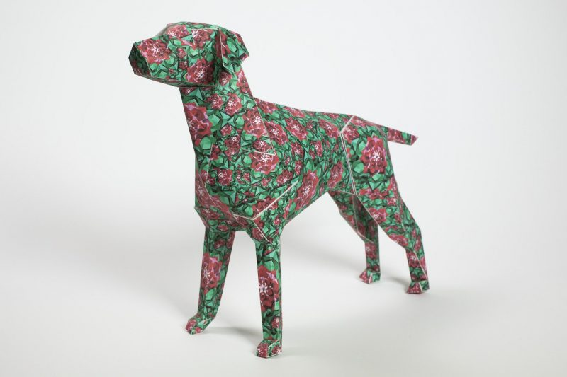 A green paper dog model in 3D form with lots of red flowers over the top of it in close clumps.