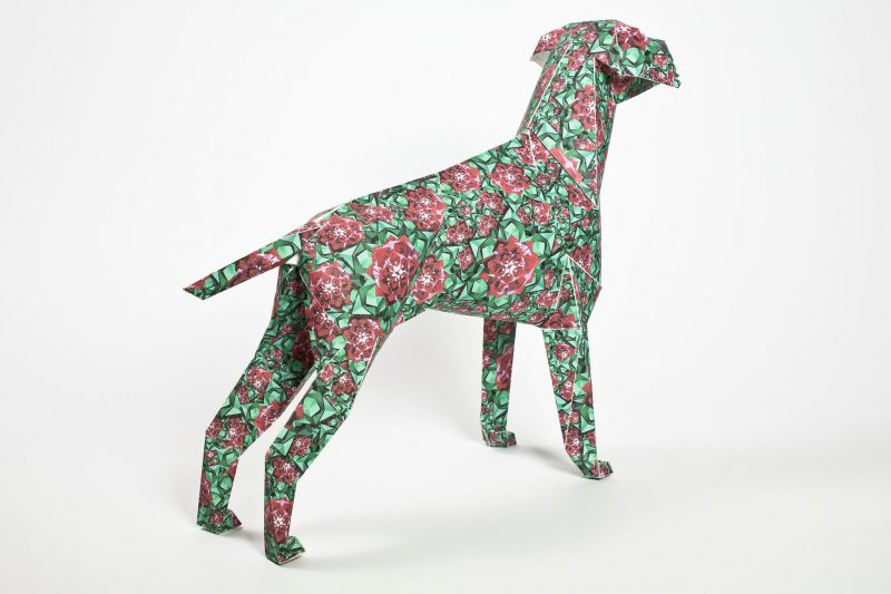 A green paper dog sculpture which has a design covered with red spring flowers.