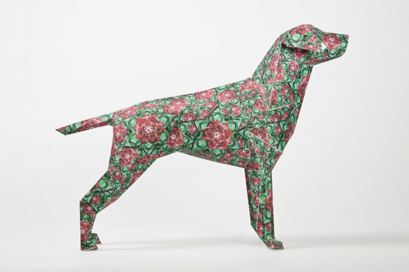 A side view of a green dog model made from paper. It has several spring red and pink flowers over the design of the model.