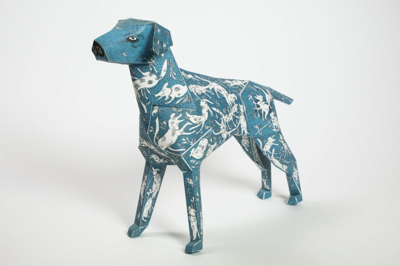 A blue paper dog model with several white smaller dogs over its body as a design pattern.