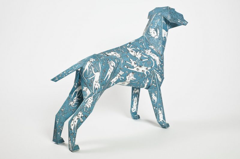 A 3D model of a blue paper dog with several smaller white dogs drawn over the model as a design.