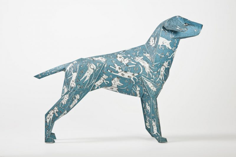 A side view of a blue paper dog model with white dogs drawn over it as a design feature.