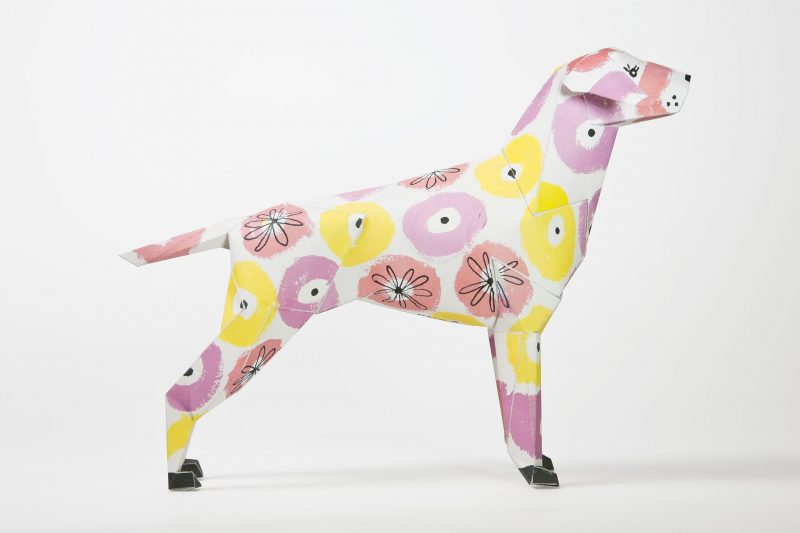 A side view of a paper dog model in 3D form. It has yellow and pink flowers on it.