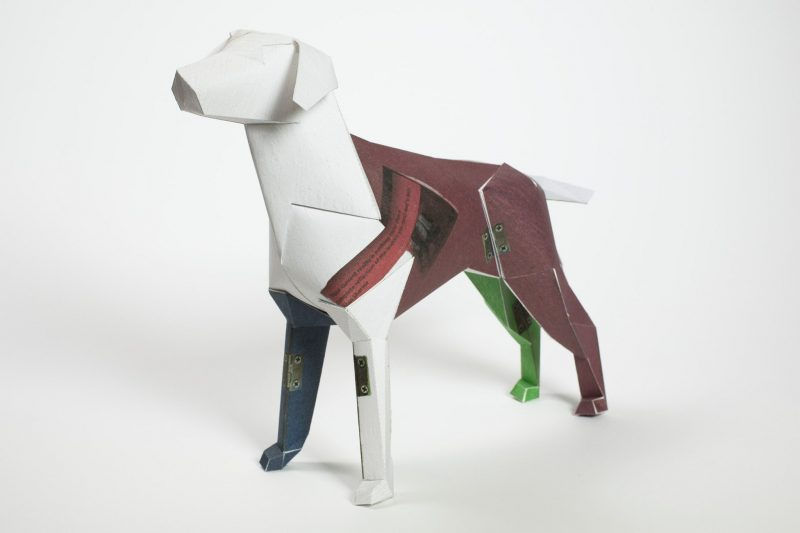 A 3D paper dog sculpture that has a burgundy back leg and white head and neck