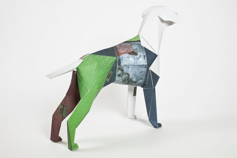 A paper dog sculpture in 3D form. It is facing away from the camera showing off its green back leg