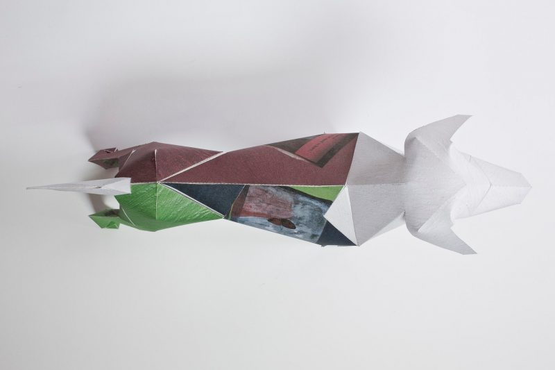 An over view of a paper dog sculpture that has a design on it that is half burgundy and half green