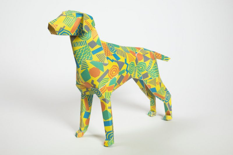 3D paper dog model with a colourful 80's style geometric pattern with a yellow background and green, orange and purple symbols.