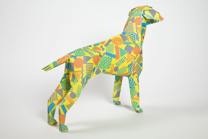 A yellow paper dog sculpture with colourful geometric 80's style shapes.