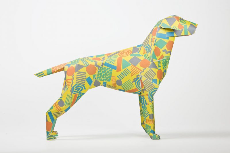 A yellow 3D paper dog sculpture with 80's style geometric shapes in orange, blue and greens