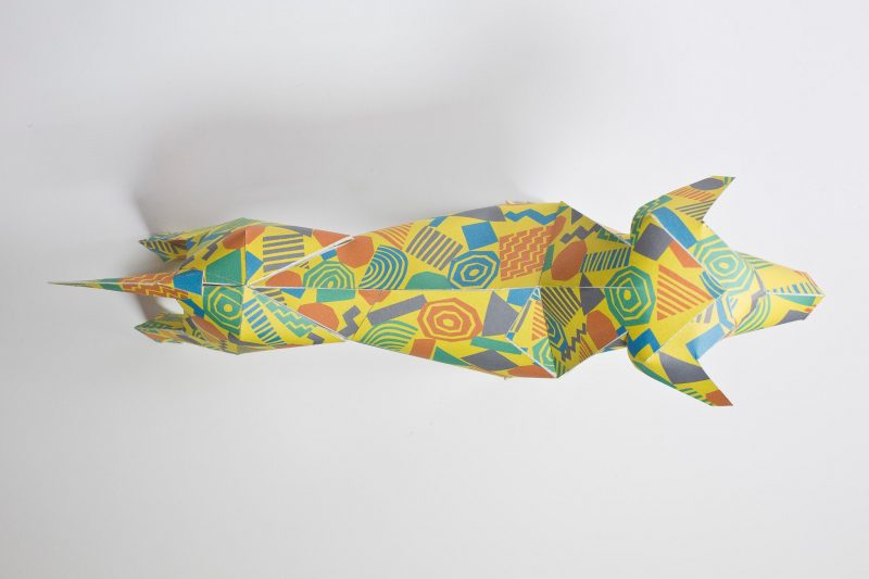 Over head view of a yellow paper dog sculpture with green, orange and blue geometric 80's shapes