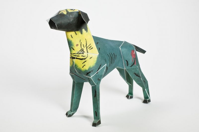 A dark blue/green paper dog model with a yellow neck