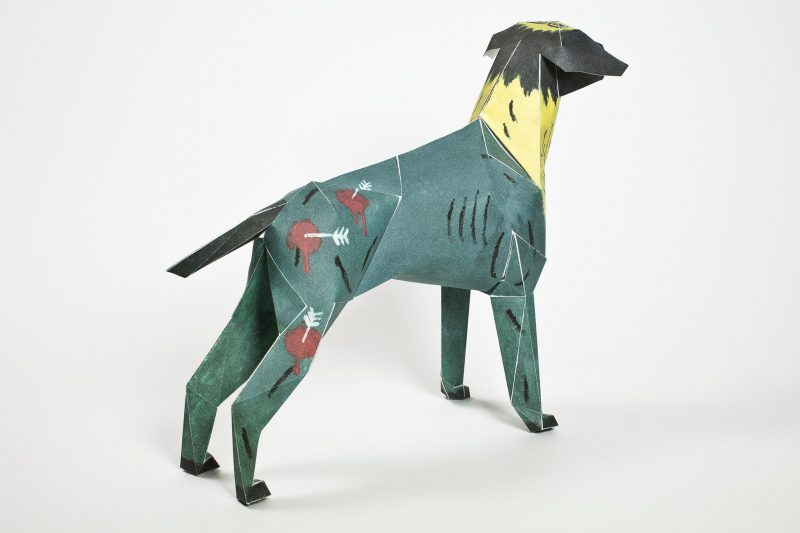 A dark blue/green 3D model of a paper dog with a yellow neck