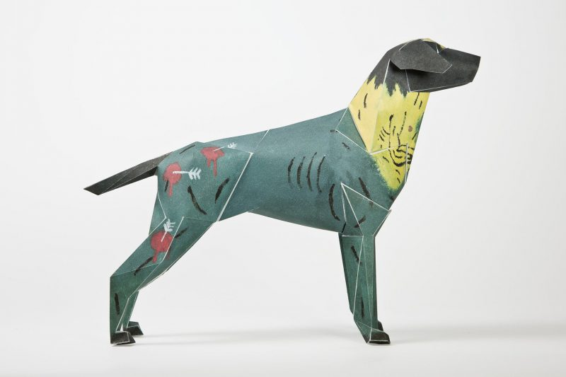 A side view of a green/blue paper dog sculpture with a yellow neck