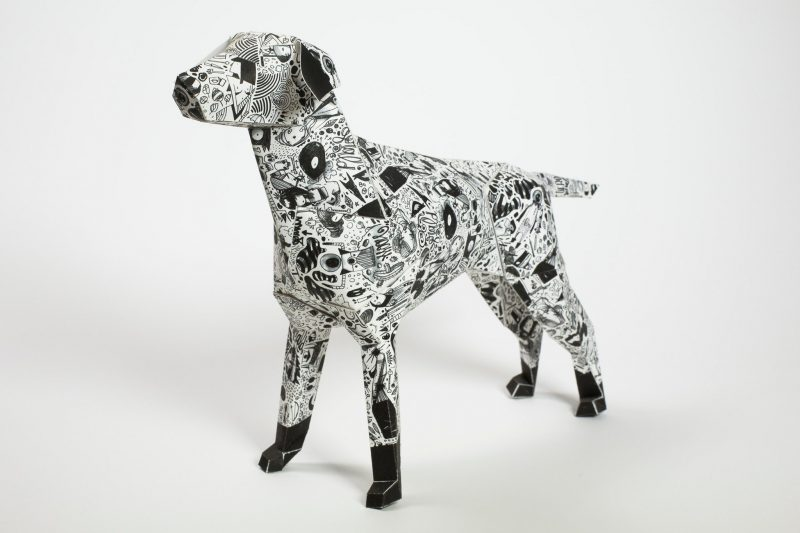 A paper dog 3D sculpture designed with a black and white coat.