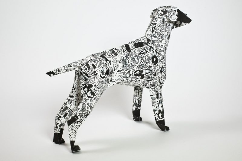 A paper dog sculpture in 3D form. It has a black and white patterned coat.