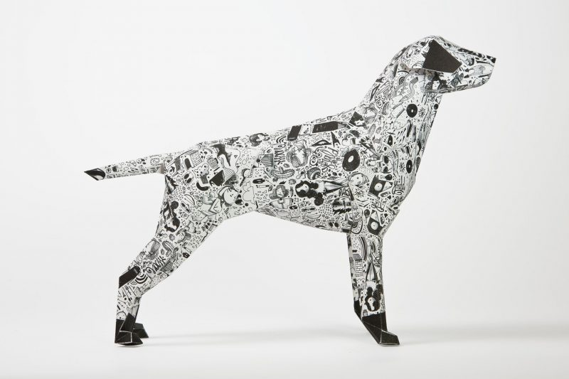 Side view of a black and white patterned paper dog in 3D form
