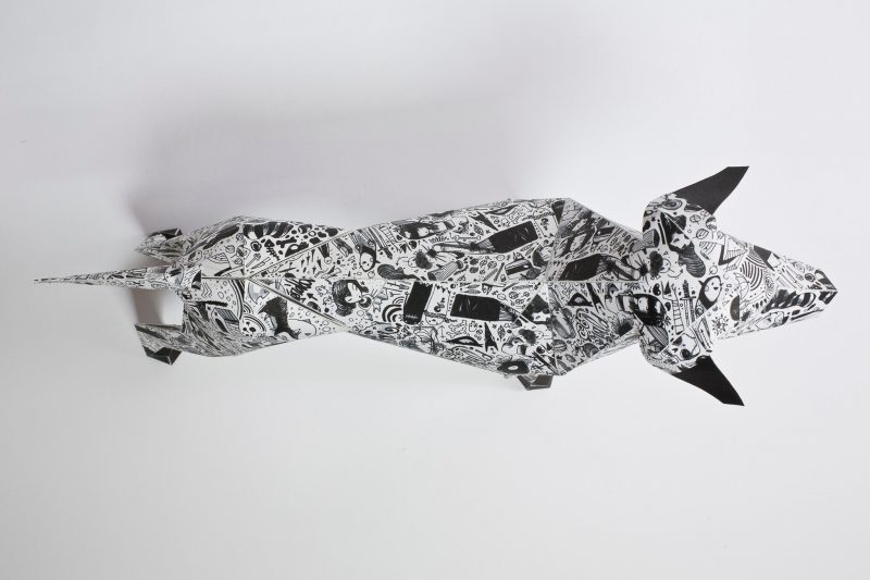 An over head view of a 3D paper dog model. It has a black and white pattern.