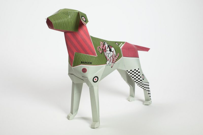 A paper dog sculpture in 3D form. It has a design on it that is prominently green pink and a light grey. It also has a logo on it of a 1950's style bikini babe and the words 'Death from Above'