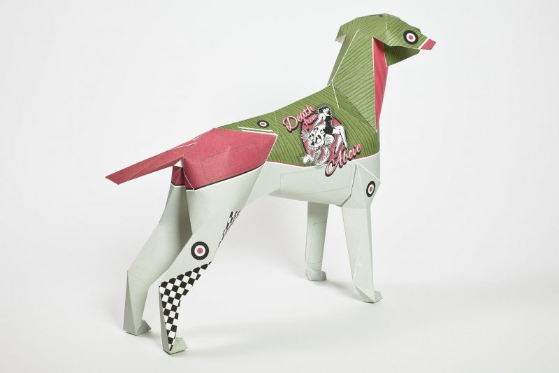 A 3D paper dog model with green, pink and light grey colouring with a logo on it. This has a black and white 1950's girl in a swimsuit on it with the words- 'Death from above' wrote around her.