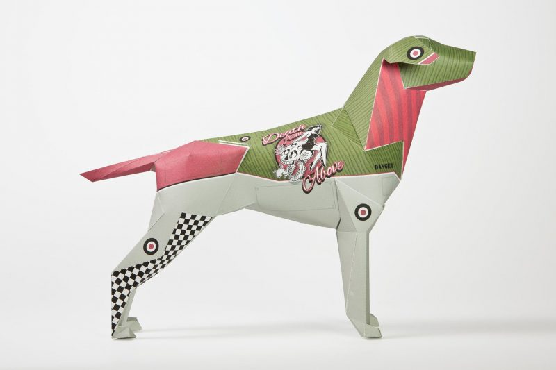 A side view of a 3D paper dog sculpture model with light grey bottom half (including legs) and a green and pink upper. It has a logo with a 1950's lady in her swimsuit and 'Death from above' wrote around her.