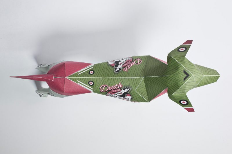 Over head view of a 3D paper dog sculpture model. You can see mostly green and a bit of salmon pink towards the back and on its tail.