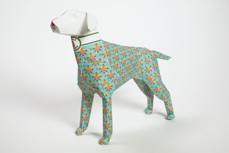 A paper dog 3D sculpture. With a light green background and a orange flowers on top of it.