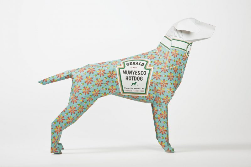 A side view of a 3D paper dog sculpture model with a light green background with orange flowers. It also has a logo on its coat that resembles the Heinz logo but instead has the words- ' GERALD- MUNYE&CO HOTDOG' wrote on it.