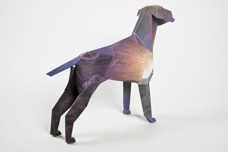 A 3D model of a paper dog sculpture with a design going from brown to purple oer its body.