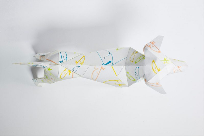 Over view of a paper dog sculpture with smaller dog faces as a design over it.
