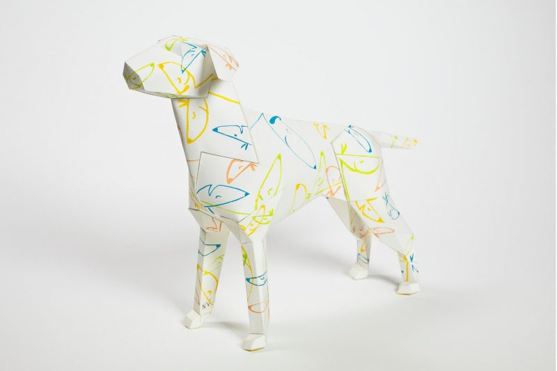 Paper dog sculpture with blue and yellow cartoonish line drawings of dogs situated all over it.