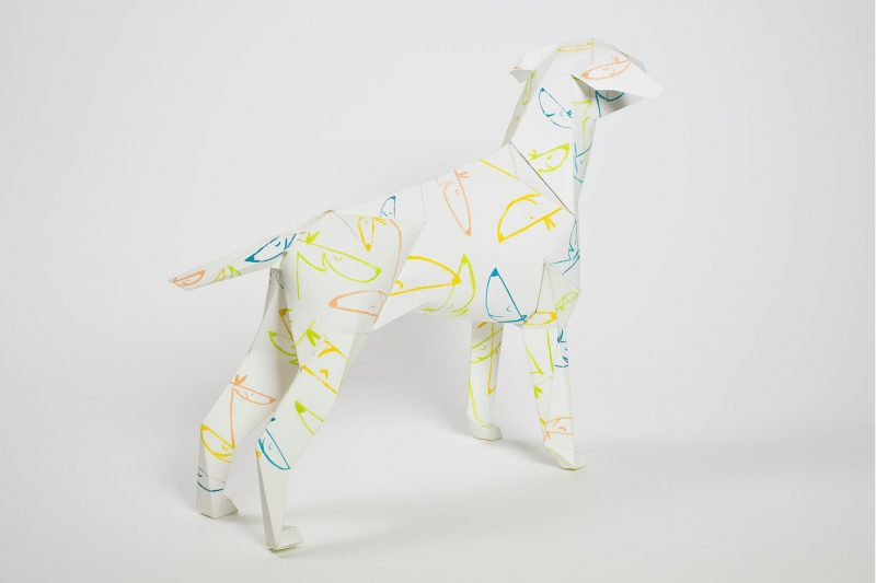 A model of a 3D dog sculpture made from paper with line drawings of blue and yellow dog faces over its head, legs, body and tail
