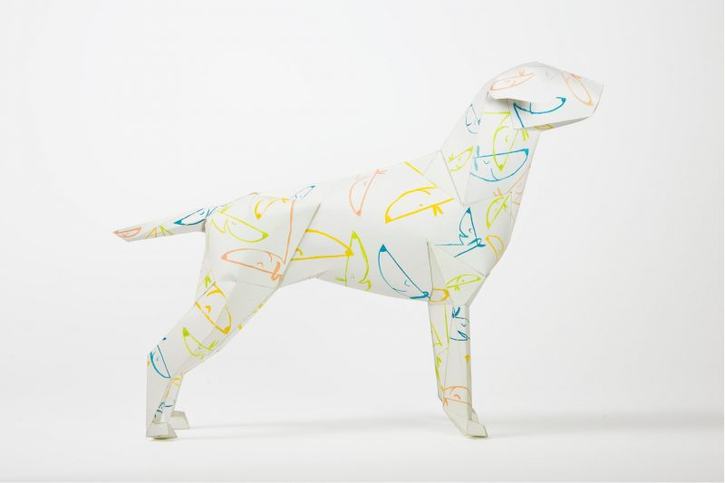 A side view of a paper dog sculpture in 3D. it has a pattern of blue, yellow and orange line drawings of dog faces all over it.