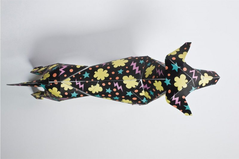 An over head view of a black paper dog model that is covered in a pattern consisting of yellow clud shapes, pink lighting bolts and blue stars.