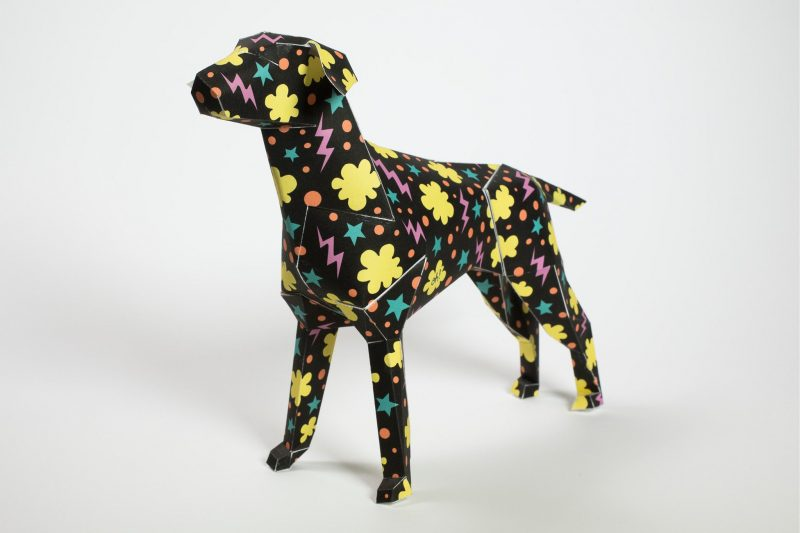 A black paper dog model sculpture with pink lighting yellow cloud shapes and blue star patterns
