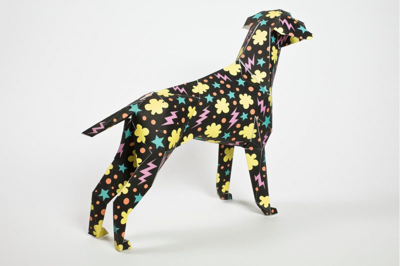A black paper dog model sculpture with pink lighting yellow cloud shapes and blue star patterns. Its is looking with its head towards the back left of the corner.