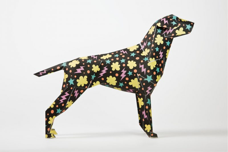 A side view of a black 3D paper sculpture of a dog that has a pattern on it. It consists of yellow cloud shapes, blue stars and pink lighting bolts.