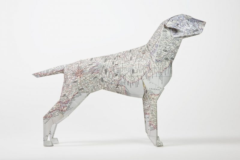 A side view of a 3D paper dog model with a detailed line map design all over its body.