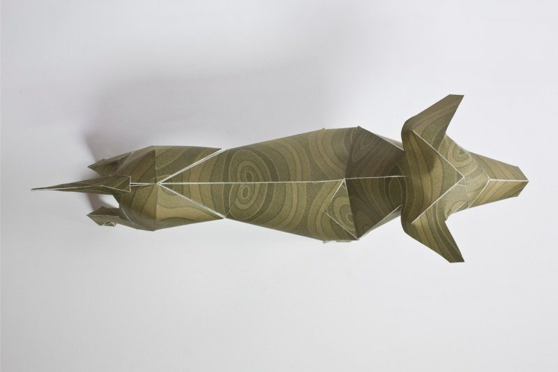An over head view of a 3D paper sculpture of a dog. It has a green/brown wood grain type pattern.