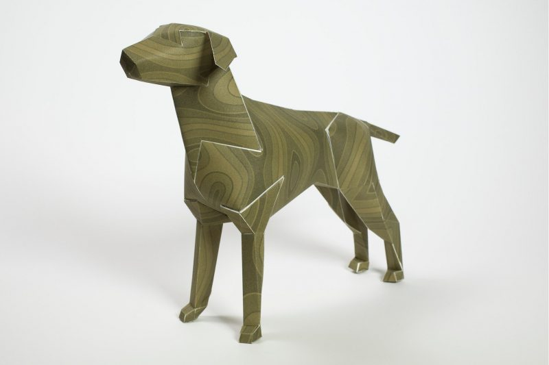 Left hand view of a paper dog (with its head pointing towards the left hand side) It has a wood style garain pattern on it in the colour greeny/brown.