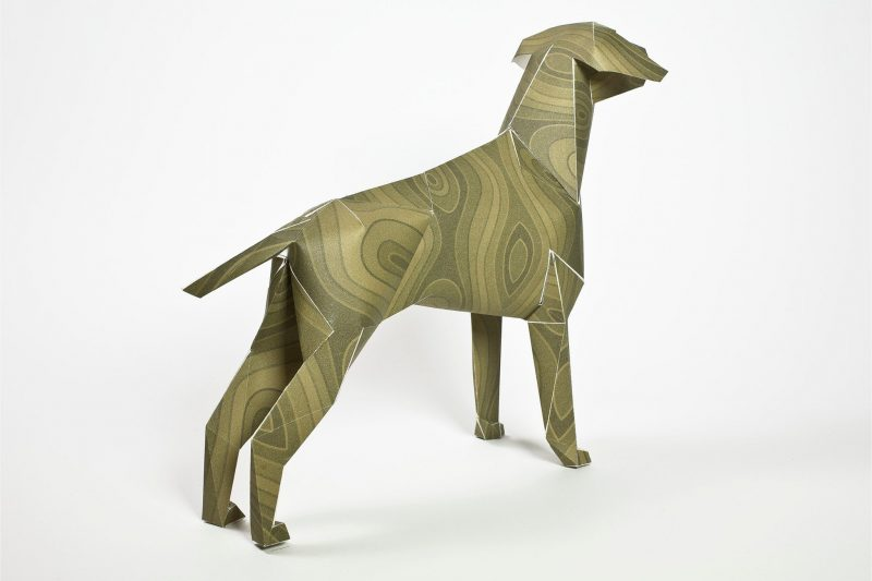 A view of a 3D paper dog sculpture with the head looking away from the camera towards the right hand side. It has a pattern on its coat which is a greeny brown wood grain type.