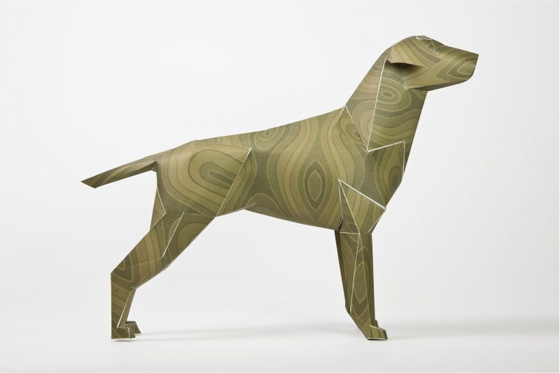 A side view of a 3D paper dog sculpture that has a green/brown pattern.